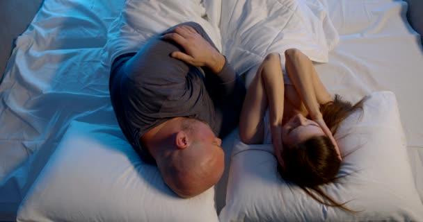 man is snoring in sleep, his wife is closing ears, pushing him