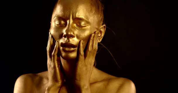 Nahaufnahme Porträt eines sanften nackten Mädchens, sie steht im Atelier auf schwarzem Hintergrund, sie hat ein goldenes Pigment auf der Haut. sie posiert, macht Massagebewegungen mit den Händen im Gesicht.