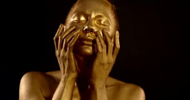 Detailní portrét něžné nahé dívky, je v ateliéru na černém pozadí, na kůži má zlatý pigment. pózuje, dělá pohyby s rukama na tváři.