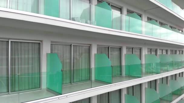 detailní záběr z výšky krásného bílého hotelu s panoramatickými okny, průhledné balkony s židlemi.