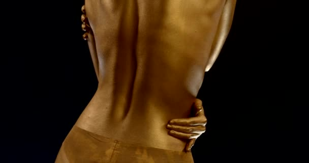 close-up of a womans back with Golden glowing skin and lingerie on a black background. the girl strokes her sides and neck