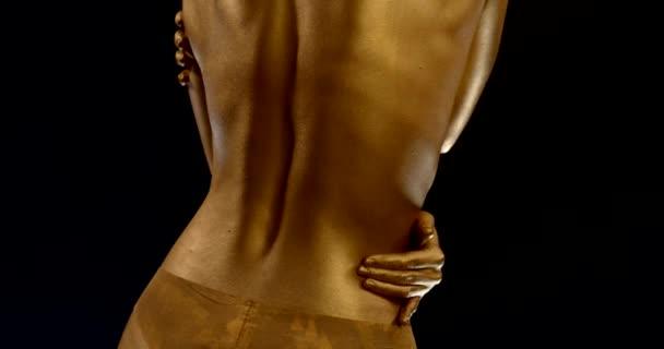 Nahaufnahme eines Frauenrückens mit goldglühender Haut und Dessous auf schwarzem Hintergrund. das Mädchen streicht sich über die Seiten und den Hals
