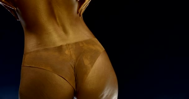 close-up of the female body with Golden skin and underwear and with a big booty and a thin waist on a black background. the girl stands with her back, turns, and strokes her hand and chest