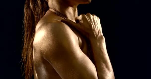 sportovní žena se zlatou pletí a lesklým spodním prádlem pózuje na černém pozadí. dotýká se rtů a brady a přejíždí si prsty po krku a rameni