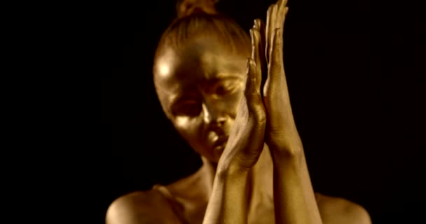 close-up of womens hands with Golden glowing skin. they slowly stroke each other, fingers intertwining, palms sliding. in the background, a girl is seen out of focus. black background