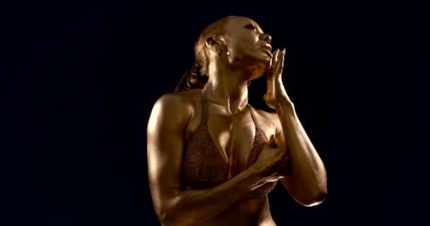 portrét ženy se zlatou pletí a zvednutými svaly v lesklém spodním prádle na černém pozadí. Přejíždí si rukou po rtech a obličeji, dívá se do kamery, otáčí se bokem, dotýká se vlasů