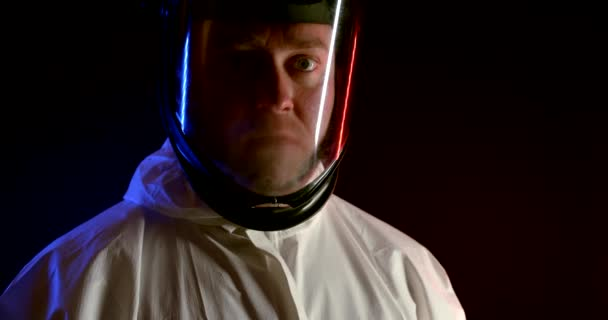 A scientist in full protective clothing. Portrait of a man in chemical and bacterial protection on a black background