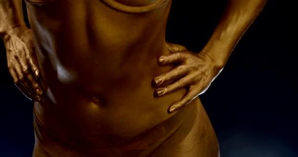 arany test-art fiatal nő fehérneműben, ő mozog csípő és has