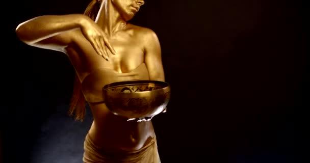 Tänzerin mit goldglänzender Haut tanzt mit tibetischer Klangschale