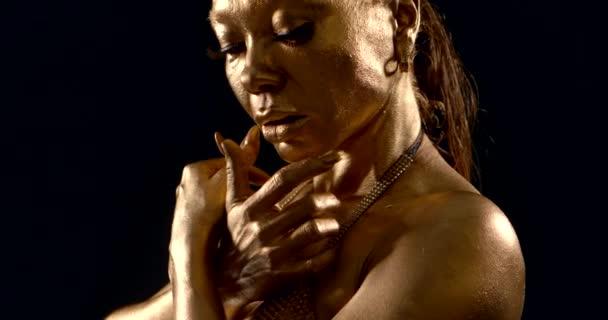 verführerische schwarze Frau ist golden gefärbt, streichelt ihre Schultern und Brüste