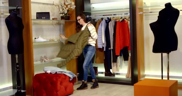 mladá žena nakupující zkouší oblečení v šatně módní obchod, uvedení teplé bundy