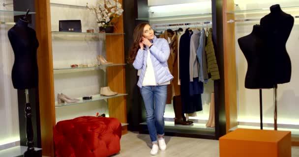 stylová mladá žena dává náušnice pro nové oblečení do šatny, tance a úsměvu