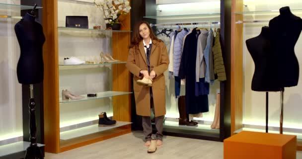 žena si dává boty na nohy v šatníku, rozepíná zip, zkouší teplé oblečení