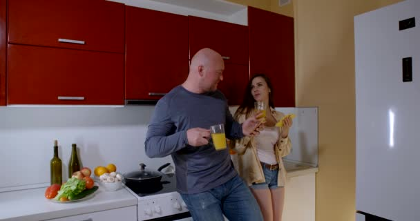 a bald middle-aged man and a young brunette with long hair are dressed in casual clothes and standing in the kitchen. they drink juice from clear glasses, hold phones in their hands, chat and laugh