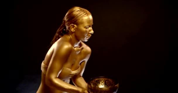 Goldene Frau mit alter tibetischer Glocke tanzt