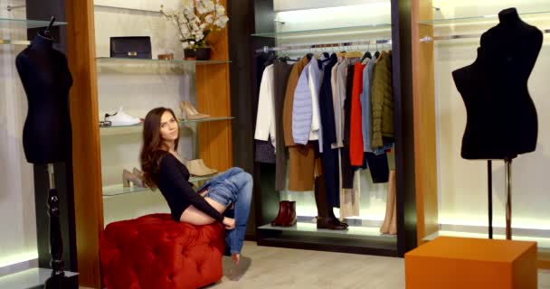 mladá hezká žena se snaží džíny v showroom oblečení obchod, uvedení kalhoty a opasek