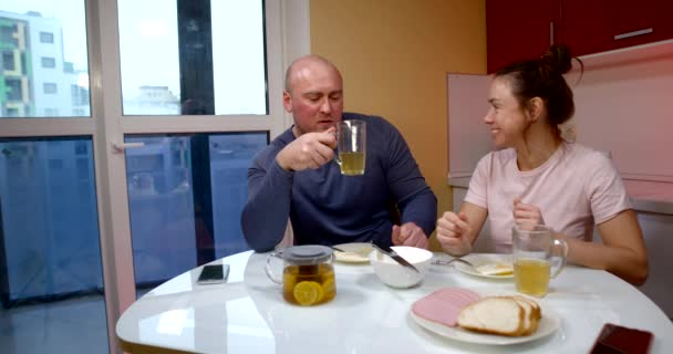 a middle-aged couple is sitting at a table in the kitchen by a large window. they have clear glasses and a pot of tea. the woman laughs, speaks, gestures. the man listens and answers