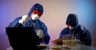Two virologists are in the lab, sitting at a table with a laptop, notes and flasks of analysis. They are wearing a blue work suit, glasses, and a mask. The second one is holding a tablet. stock vector