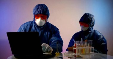 Team of virologists are working in laboratory, exploring coronavirus, two scientists dressed in protective clothes stock vector