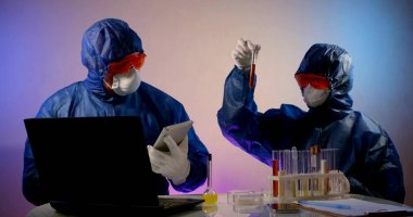 Two virologists are in the lab, sitting at a table with a laptop, notes, and flasks of analysis. They are wearing a blue work suit, glasses, and a mask. One is holding a tablet. stock vector