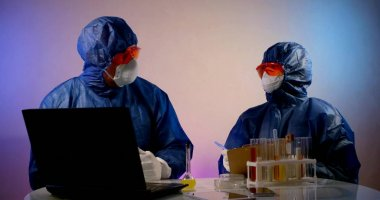 Virologists dressed in protective suits are exploring coronavirus in laboratory, looking for cure and vaccine stock vector