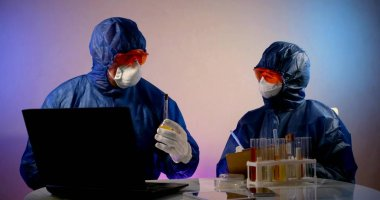 Two virologists are in the lab, sitting at a table with a laptop, notes and flasks of analysis. They are wearing a blue work suit, glasses, and a mask. The second one is holding a tablet on which stock vector