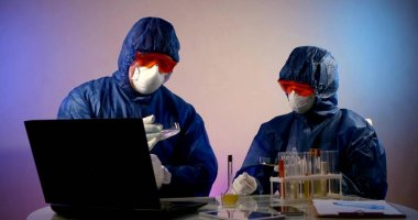 Two virologists are in the lab, sitting at a table on which there are gadgets, records, and flasks with different analyses that they are investigating. They are wearing a blue work suit, glasses, and stock vector