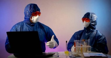 Two virologists are in the lab, sitting at a table with a laptop and flasks of analysis. They are wearing a blue work suit, glasses, and a mask. They are happy to work successfully, give each other a stock vector
