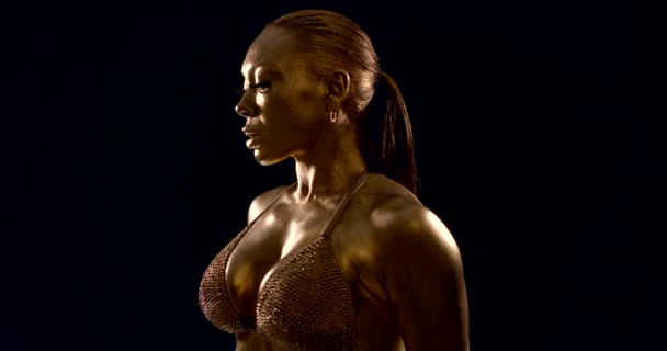 female bodybuilder is demonstrating her muscular breast and shoulder, skin is covered golden dye
