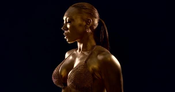 Bodybuilderin zeigt ihre muskulöse Brust und Schulter, die Haut ist mit goldenem Farbstoff überzogen