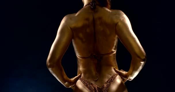 sportlicher Körper muskulöser Frau, bedeckt mit goldenem Farbstoff, Rückansicht