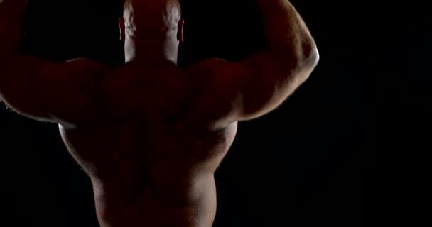 velký svalnatý plešatý muž s bronzovou kůží pózuje zády na černém pozadí. zvedne paže, ohne je a napne ramena, pak ukáže nejširší svaly