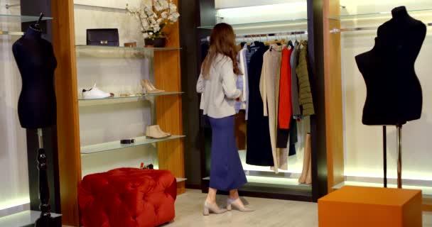 mladá módní dáma je uvedení kabát na její šaty v šatně v jejím bytě