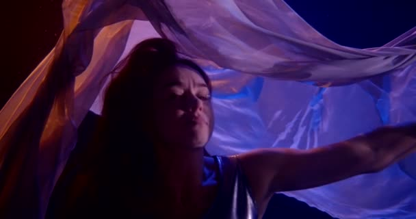 an adult pretty woman with red hair is swimming in a dress under water in a neon light