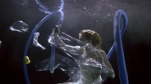 A young slender girl is under water on a dark background in a polluted environment, polyene bags floating around her, in which she is entangled, corrugated pipes, plastic bottles and glasses.