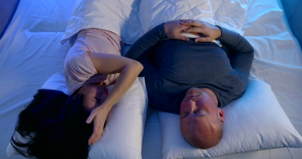 nervous woman and calm man are lying in bed at night time, try to sleep, noise from neighbors