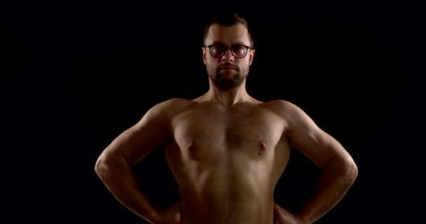 dospělý nahý muž s brýlemi stojí v tmavé místnosti a předvádí svaly trupu