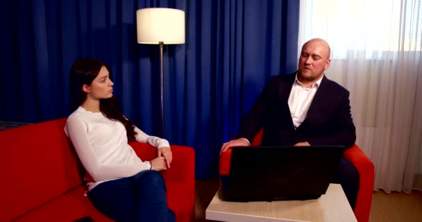 a dark-haired girl is sitting on a red sofa, next to her is a small table on which lies a laptop and a phone, next to it is a red chair on which a bald man in a suit is sitting. They communicate.