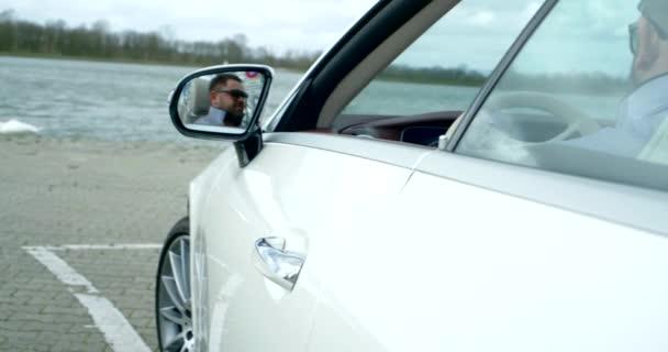 muž středního věku s tmavými vlasy sedí v bílém autě a zavírá dveře. obličej muže s brýlemi se odráží ve zpětném zrcátku. pohled zezadu