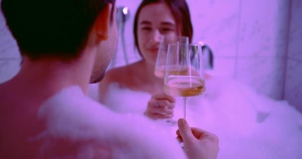 Ein Nahaufnahme-Porträt eines jungen Liebespaares, das in einer großen, mit Schaum gefüllten Whirlpool-Badewanne sitzt und Champagner trinkt, küsst, kommuniziert, lächelt und lacht..
