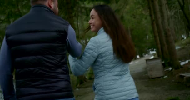 A loving couple in a forest among trees against the background of a pond and green nature, smiling, laughing, wearing jeans and jackets. They jump, rejoice, hold hands.