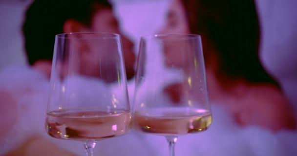 Verliebte küssen sich im Badezimmer mit Schaum, zwei Gläser mit Champagner im Vordergrund