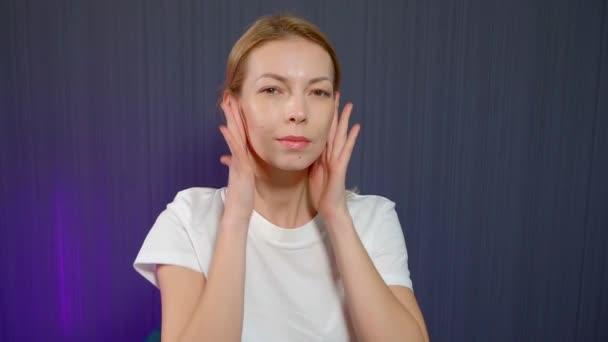 dospělá žena si masíruje obličej, masíruje a hladí tváře, omlazuje