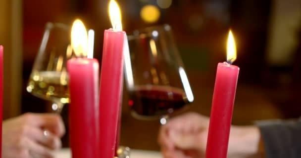 romantikus vacsora szerelmesek étteremben, csörömpölés poharak borral, közelkép
