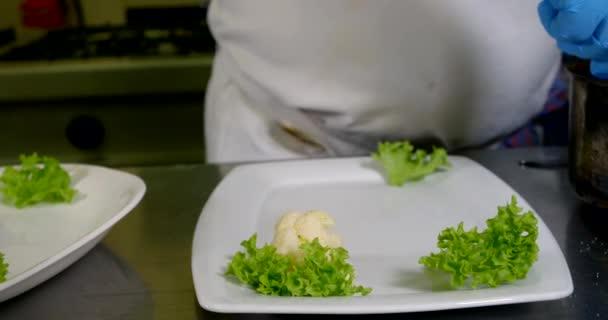 Detailní záběr kuchařských rukou, které jsou krásně rozložené zeleně, salát, zelenina: brokolice květák na talíři v kuchyni, na rukou má modré rukavice.