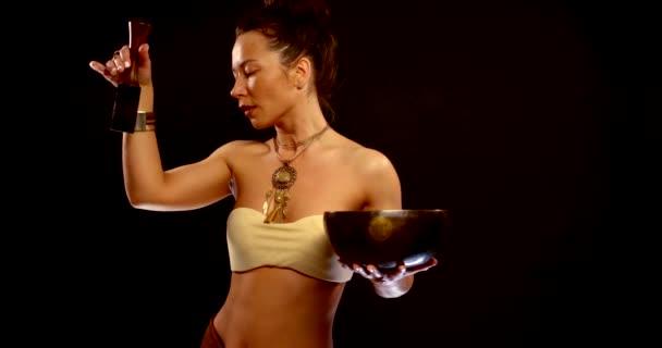 moderne Frau praktiziert Meditation mit tibetischer stehender Glocke, Tanz mit Schale