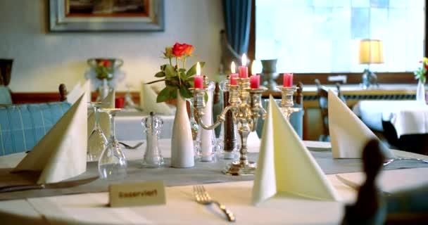 Nahaufnahme eines Tisches in einem Restaurant mit Gläsern, Geräten, Servietten und Kerzen. die Kamera fliegt herum