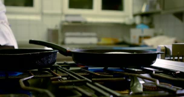 střední plán profesionální kuchyně s plynovým sporákem a dvěma pánvemi na oheň