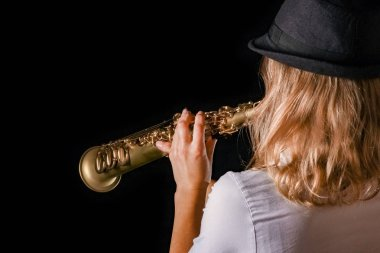 soprano saxophone in the hands of a girl on a black background