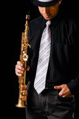 soprano saxophone in the hands of a guy on a black background
